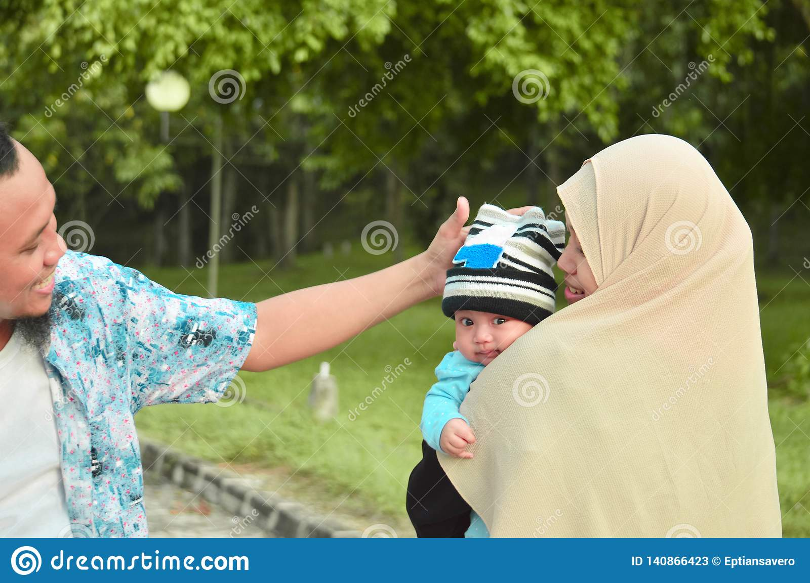 Happy Muslim`s Family Walking At Outdoor Park Holding A Baby