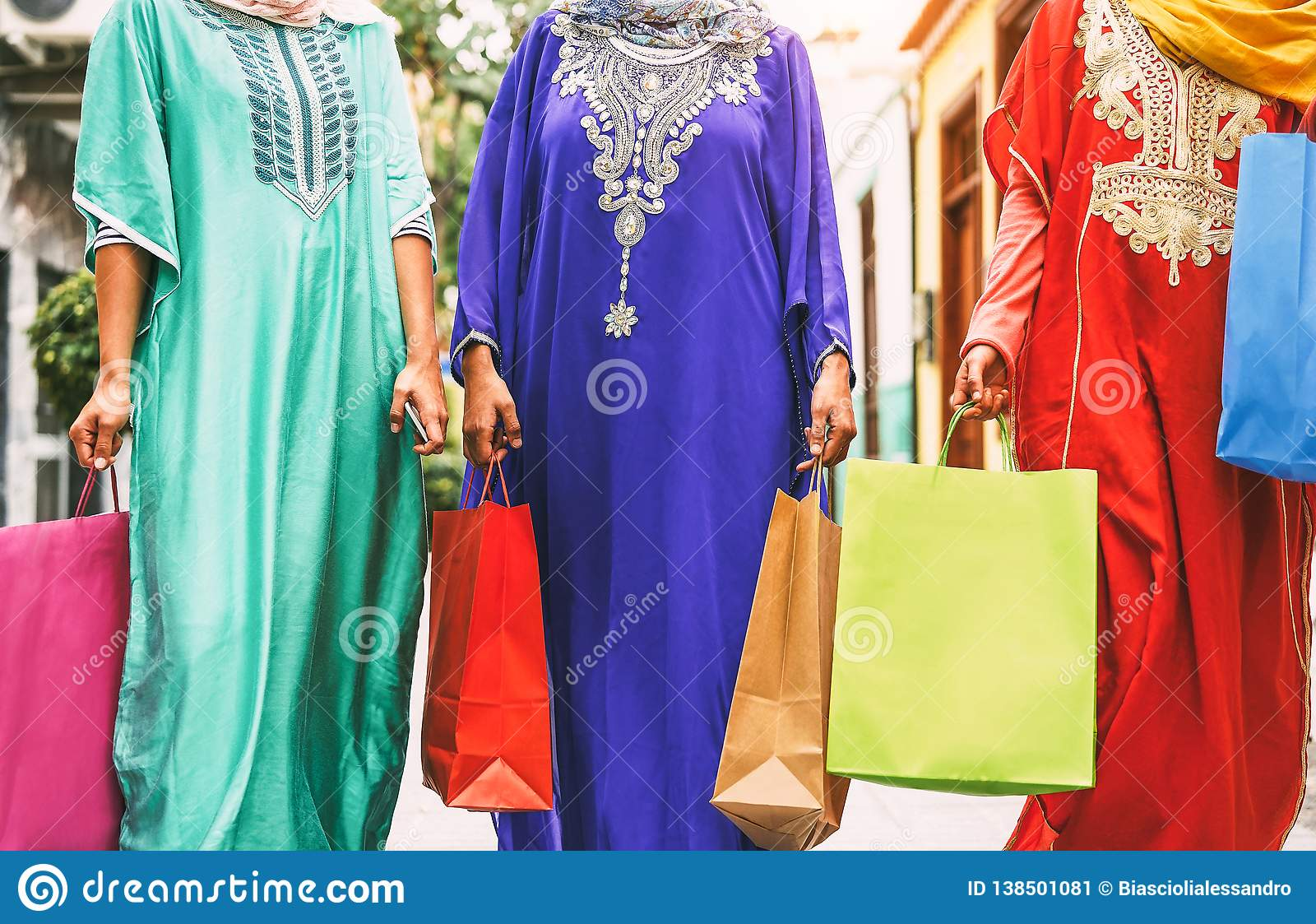 Happy Muslim women doing shopping in the city center - Arabian teen girls having fun buying new traditional Arab clothes in mall