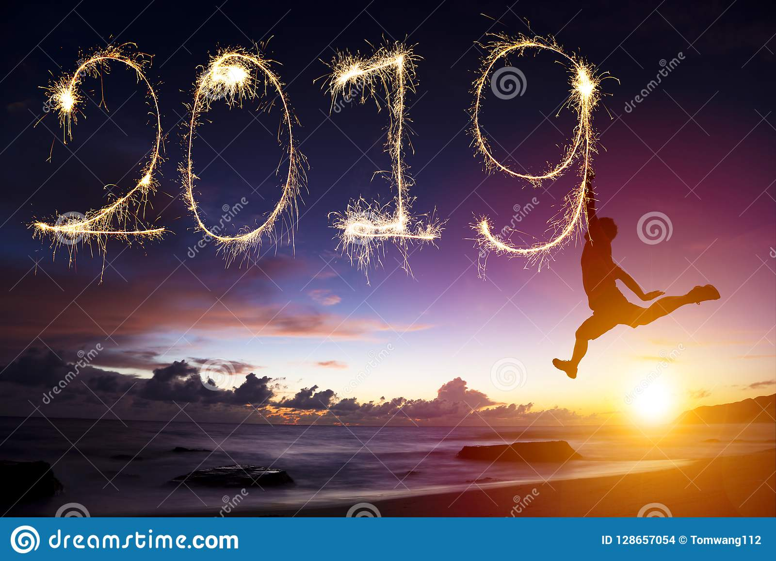 new year 2019. man jumping and drawing on beach