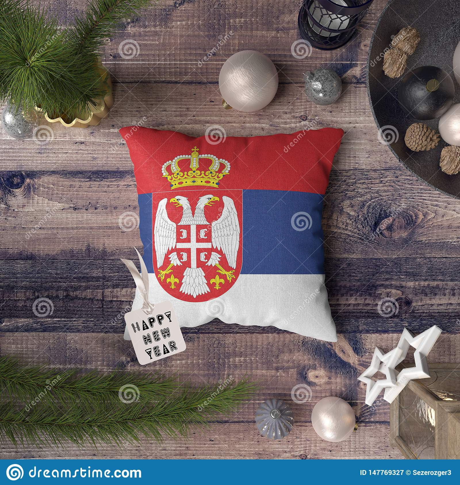 Happy New Year tag with Serbia flag on pillow. Christmas decoration concept on wooden table with lovely objects