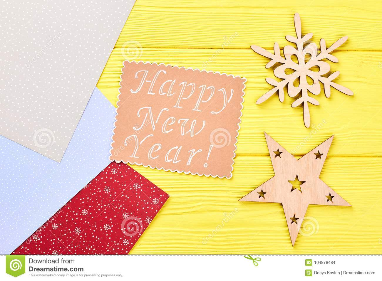 happy new year wooden background patterned colored craft paper paper message with text happy new year carved wooden christmas ornaments top view