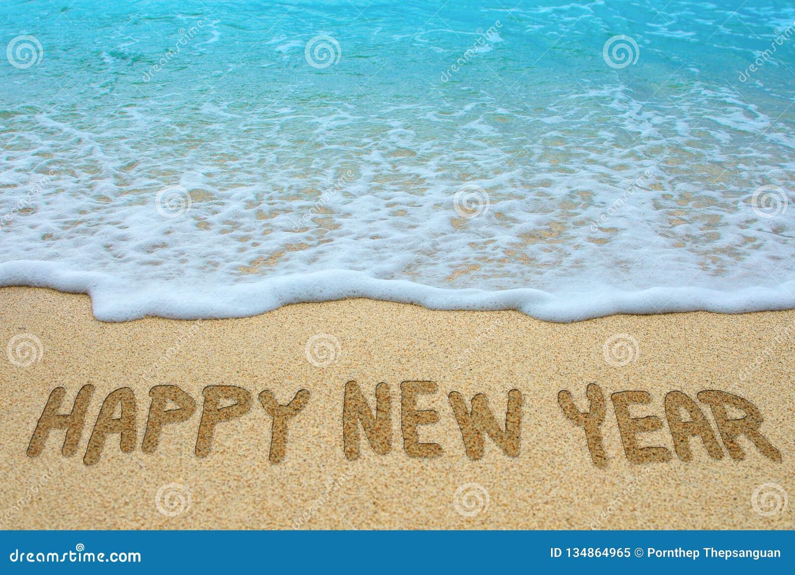 Happy new year written on sandy beach