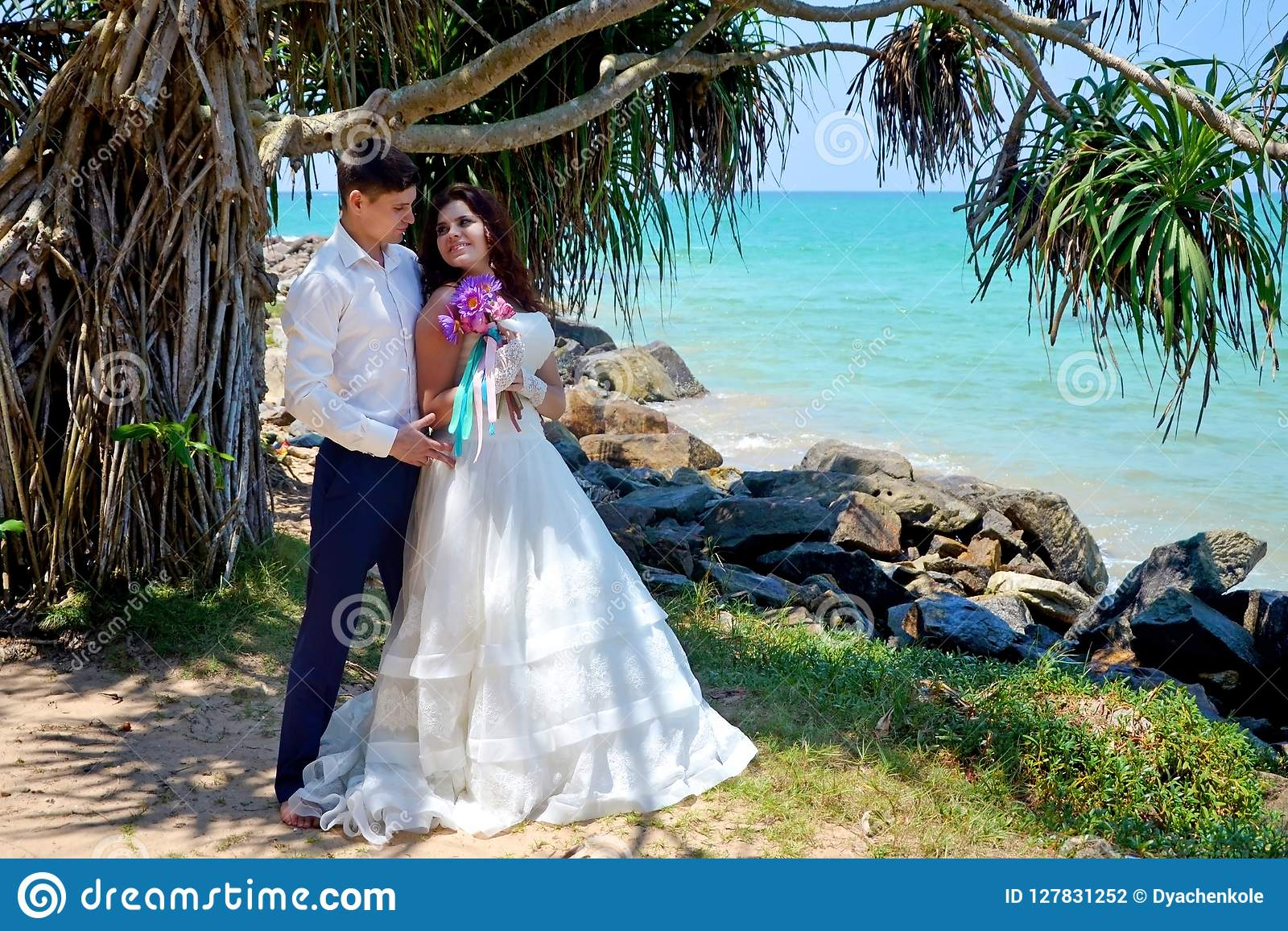 Happy newlywed couple in love are standing on the beach. Wedding and honeymoon in the tropics on the island of Sri Lanka.