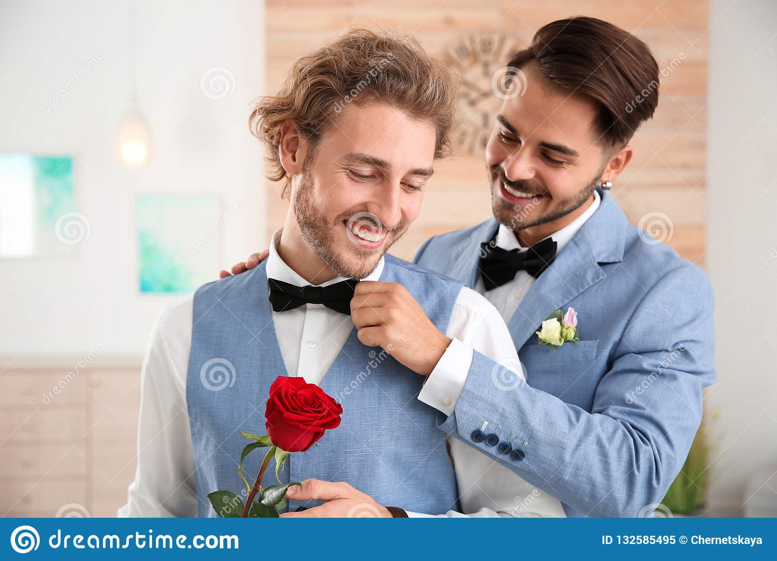 Happy newlywed gay couple with flower