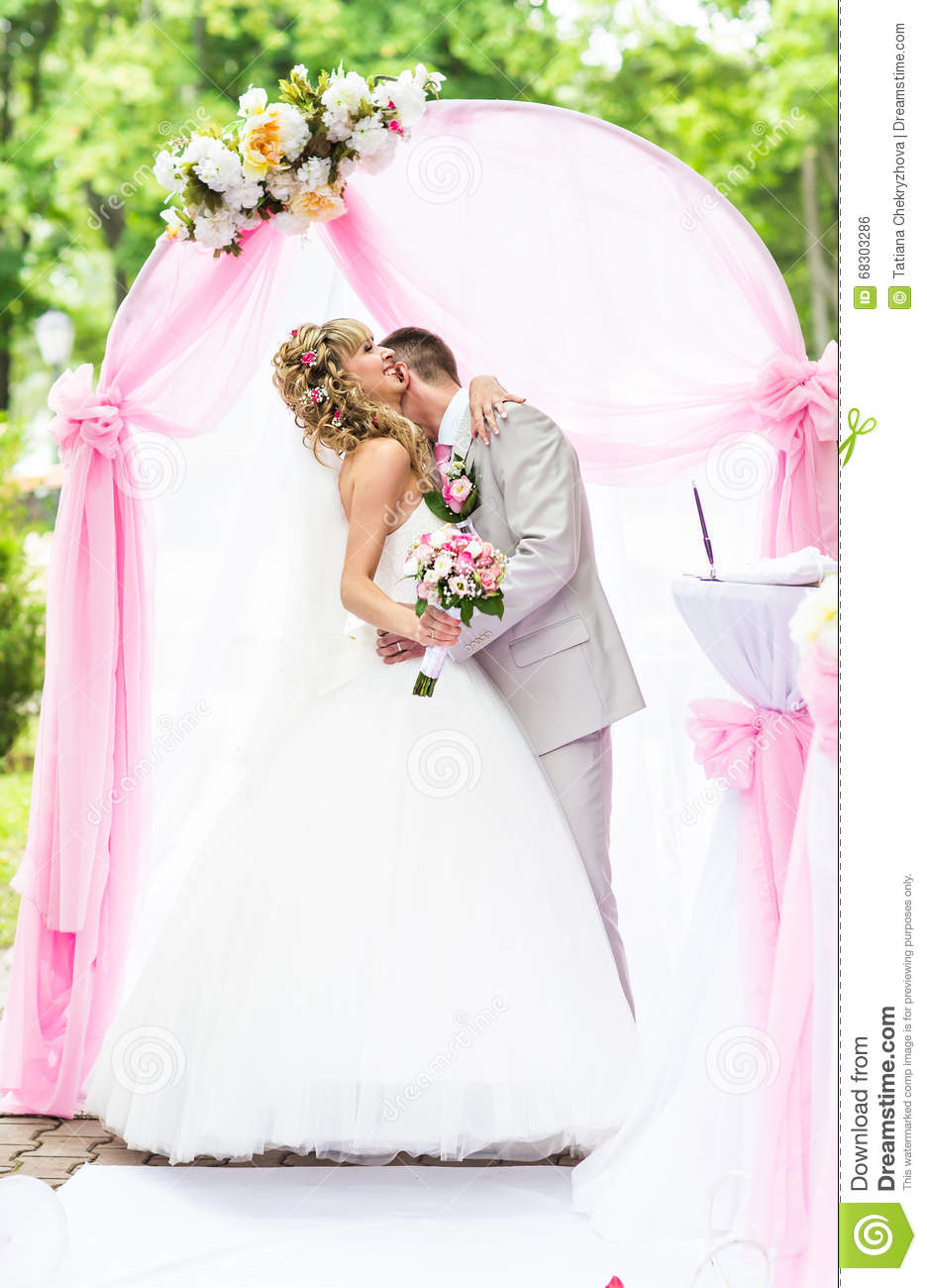 Happy Newlywed Romantic Couple Kissing At Wedding Aisle With Pink ...