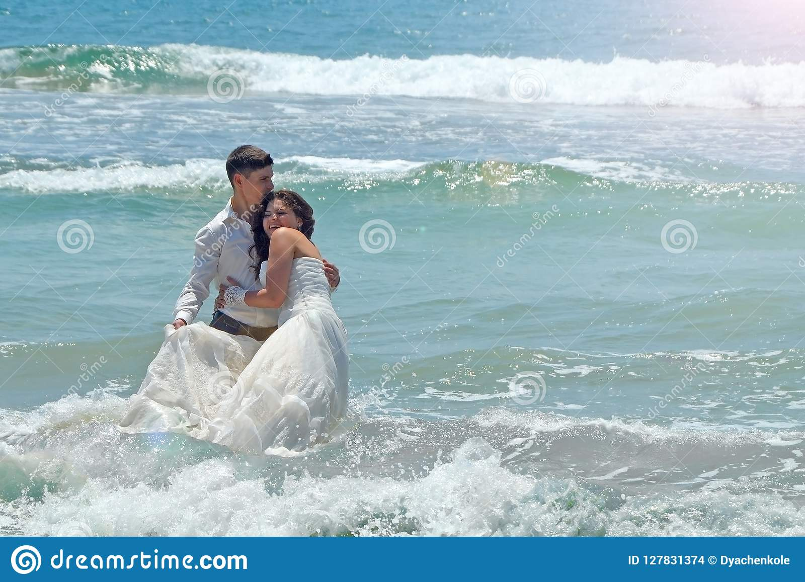 Happy newlyweds hug and laugh in the waters of the Indian Ocean. sunny wedding day and honeymoon in the tropics on the island