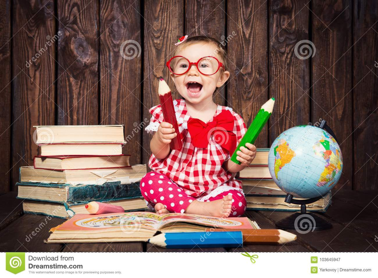 Happy a nice little girl with glasses and pencils against the background of books and a globe