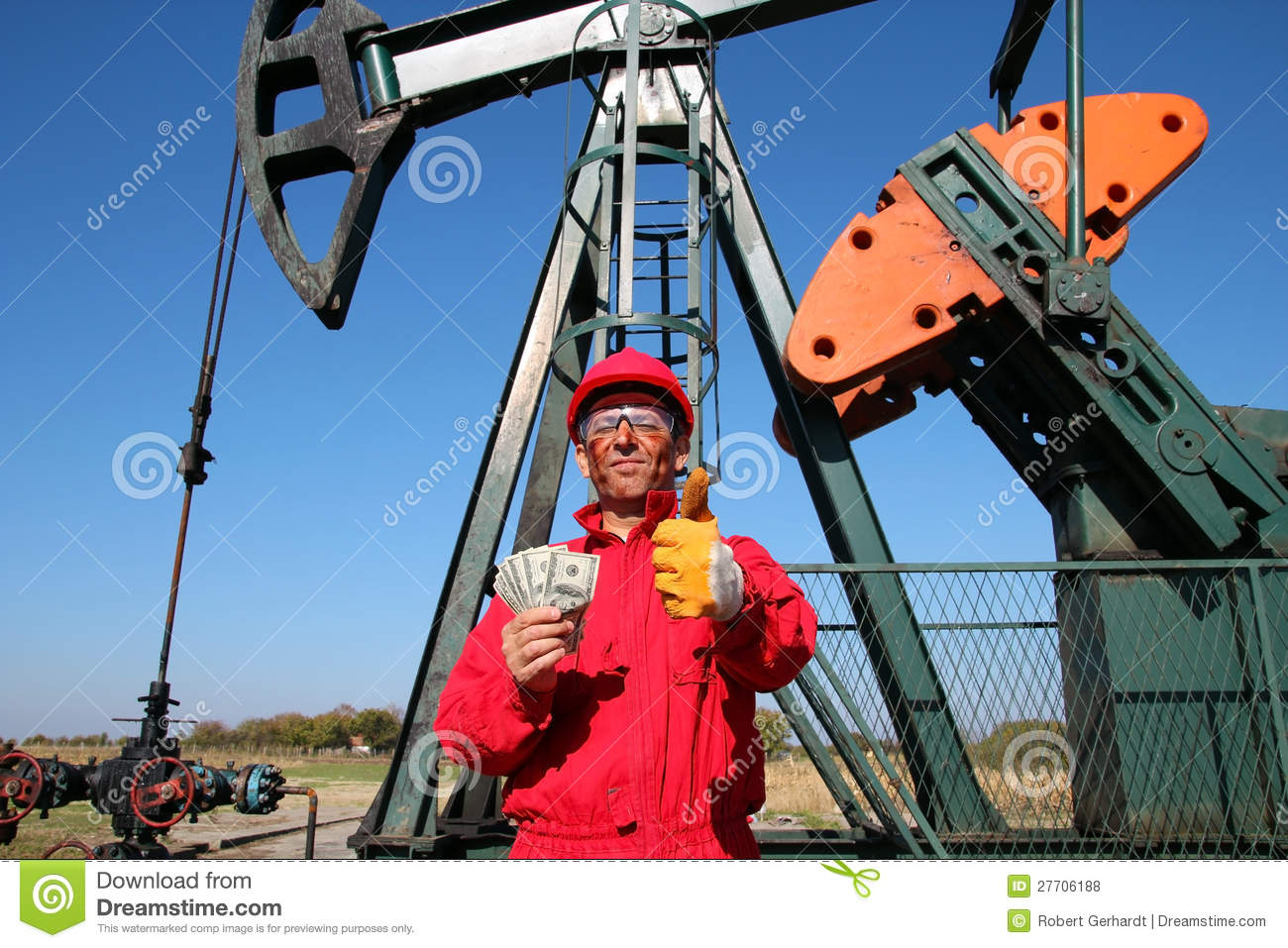 Happy Oil Worker With Money And Pump Jack Stock Photo