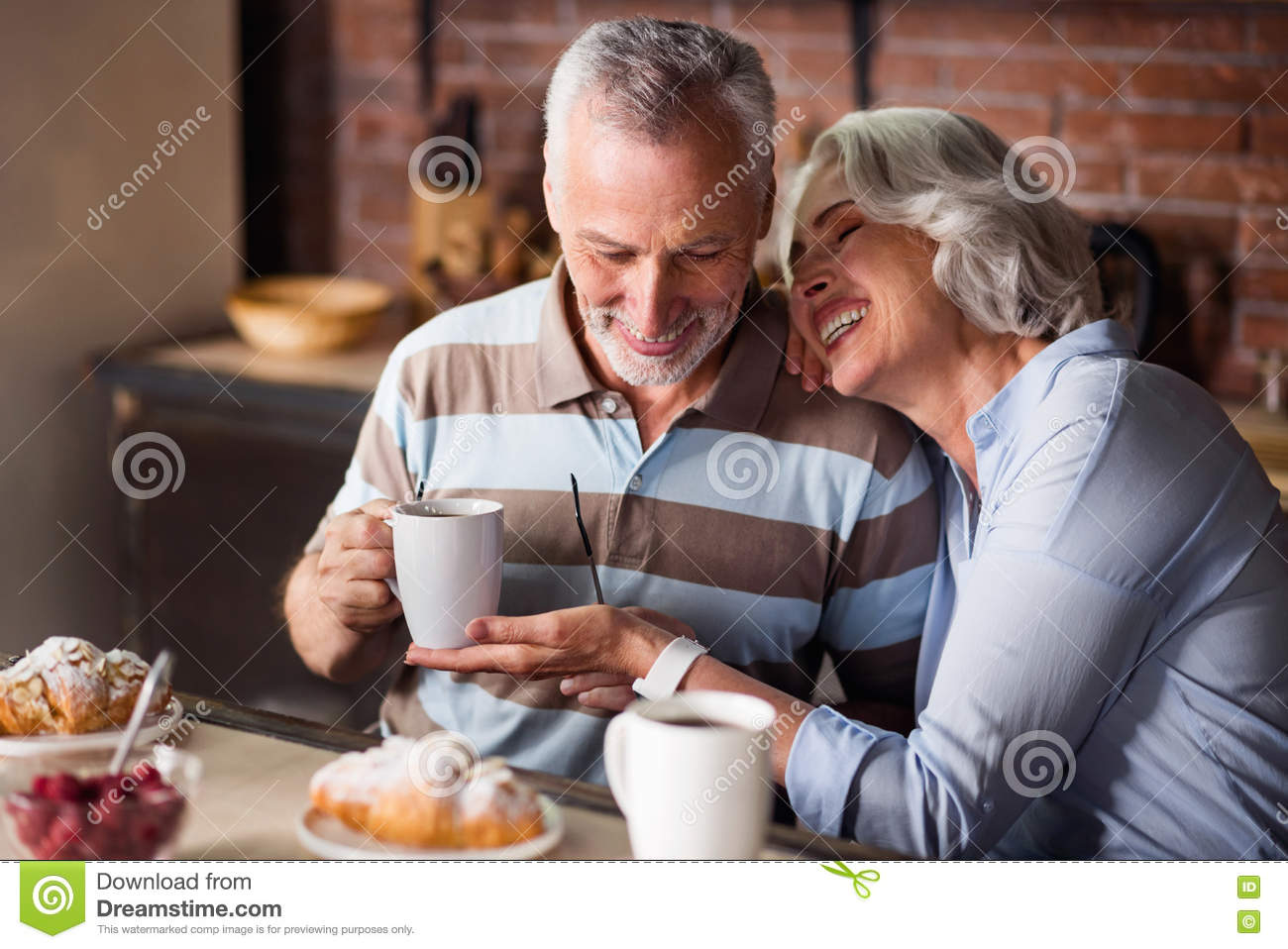 Smiling granny and grandpa holding white cups with tea and coffee during  breakfast
