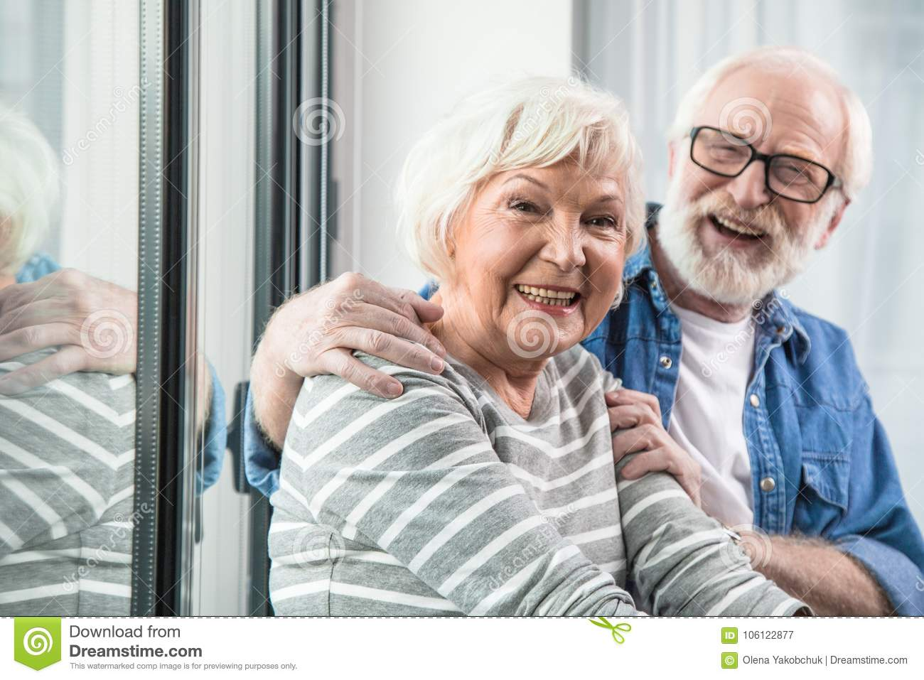 5e8302bc3a Waist up portrait of two old cheerful pensioners smiling at camera. Husband  is tenderly hugging wife while sitting at window