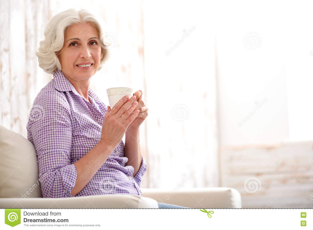 happy old woman drinking beverage at home stock image - image of