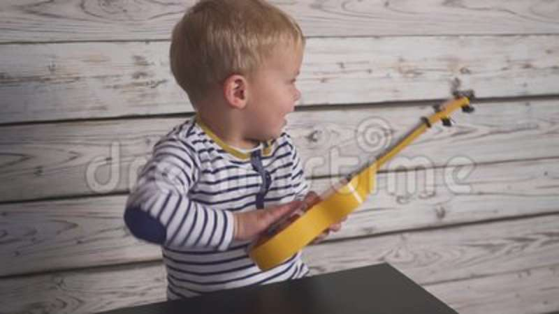 Happy One Year Old Boy Plays His Guitar Or Ukulele And Sings Songs, Sitting  In The Wooden Room. Stock Video - Video of hobby, male: 129824641