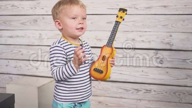 Happy One Year Old Boy Plays His Guitar Or Ukulele And Sings Songs, Sitting  In The Wooden Room. Stock Video - Video of playing, people: 129823825
