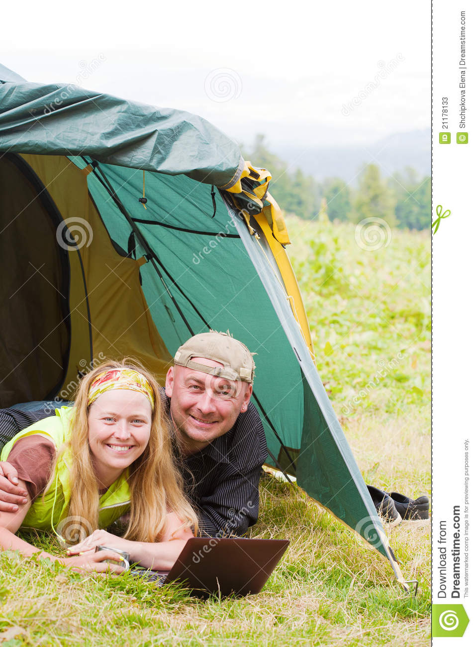 Happy pair in tent works on a laptop