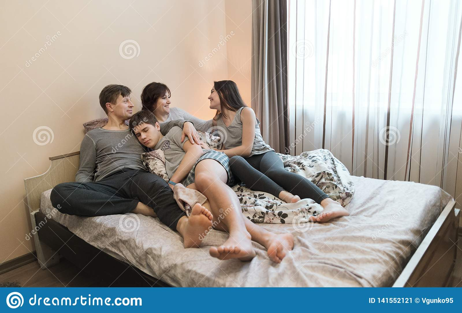 Family Relaxing Together In Bedю Happy family concept