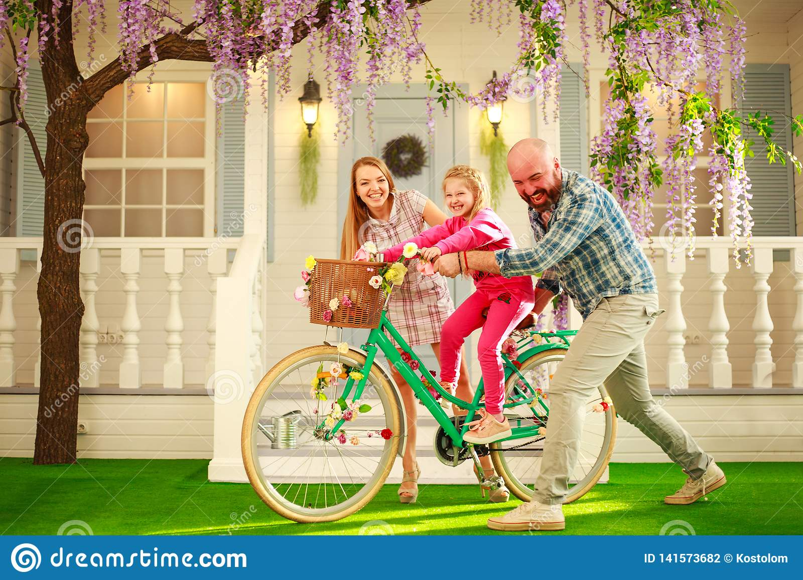 Happy parents with a child, daughter, learn to ride a bike, family lifestyle summer vacations at home