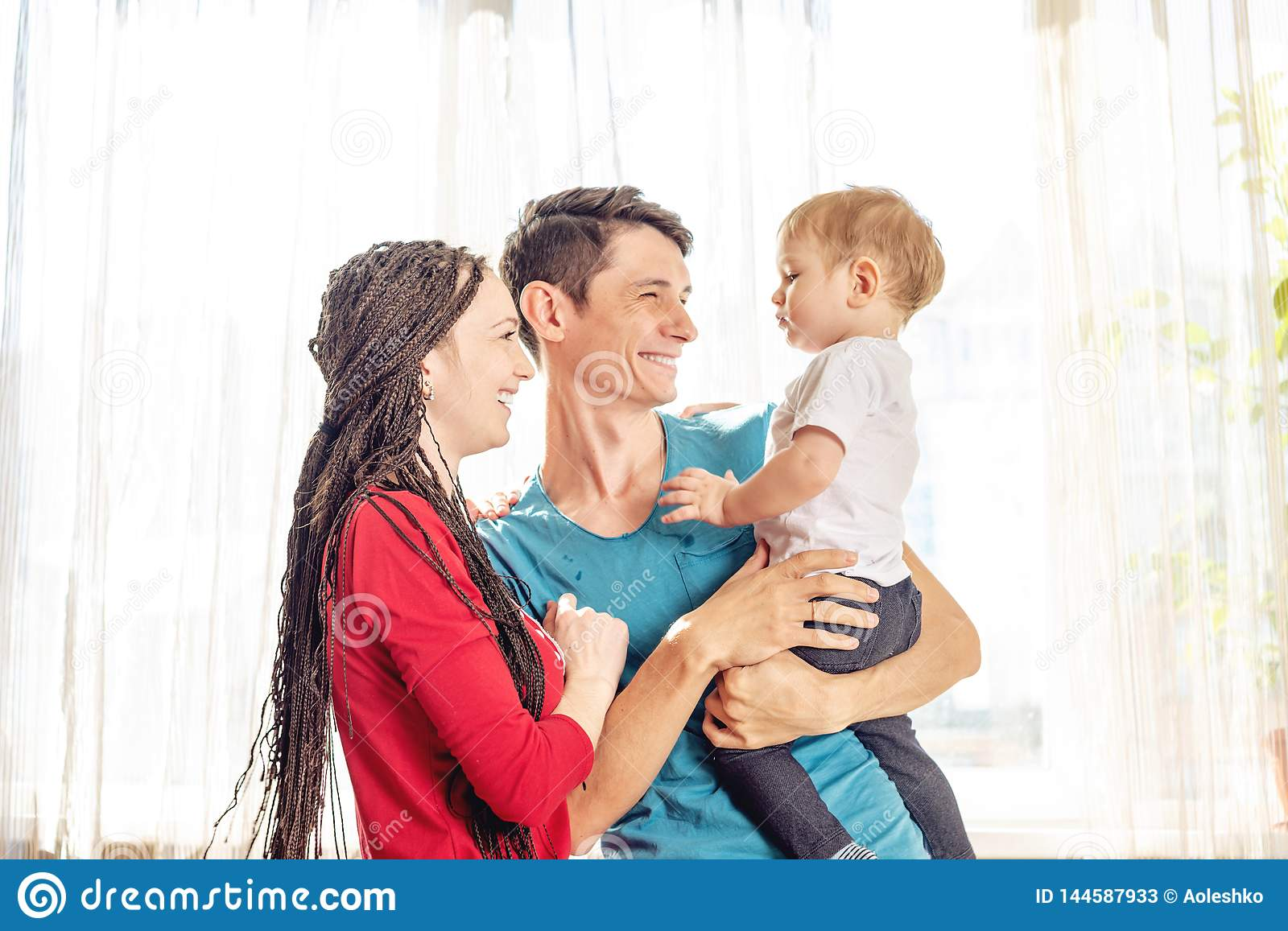 Happy parents father and mother playing with baby son at the on window background. Cheerful and modern young family
