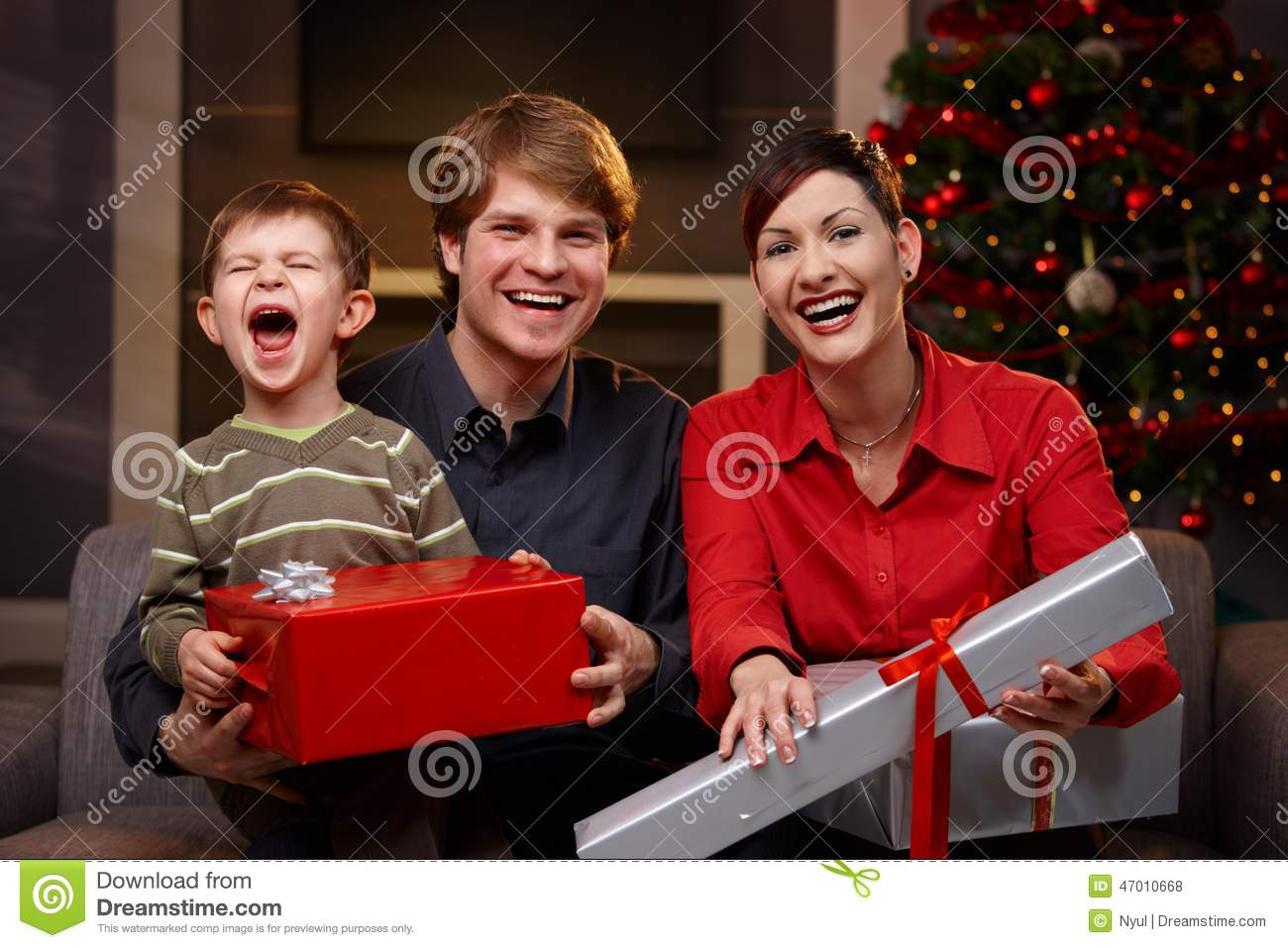 Happy parents and son with christmas gifts