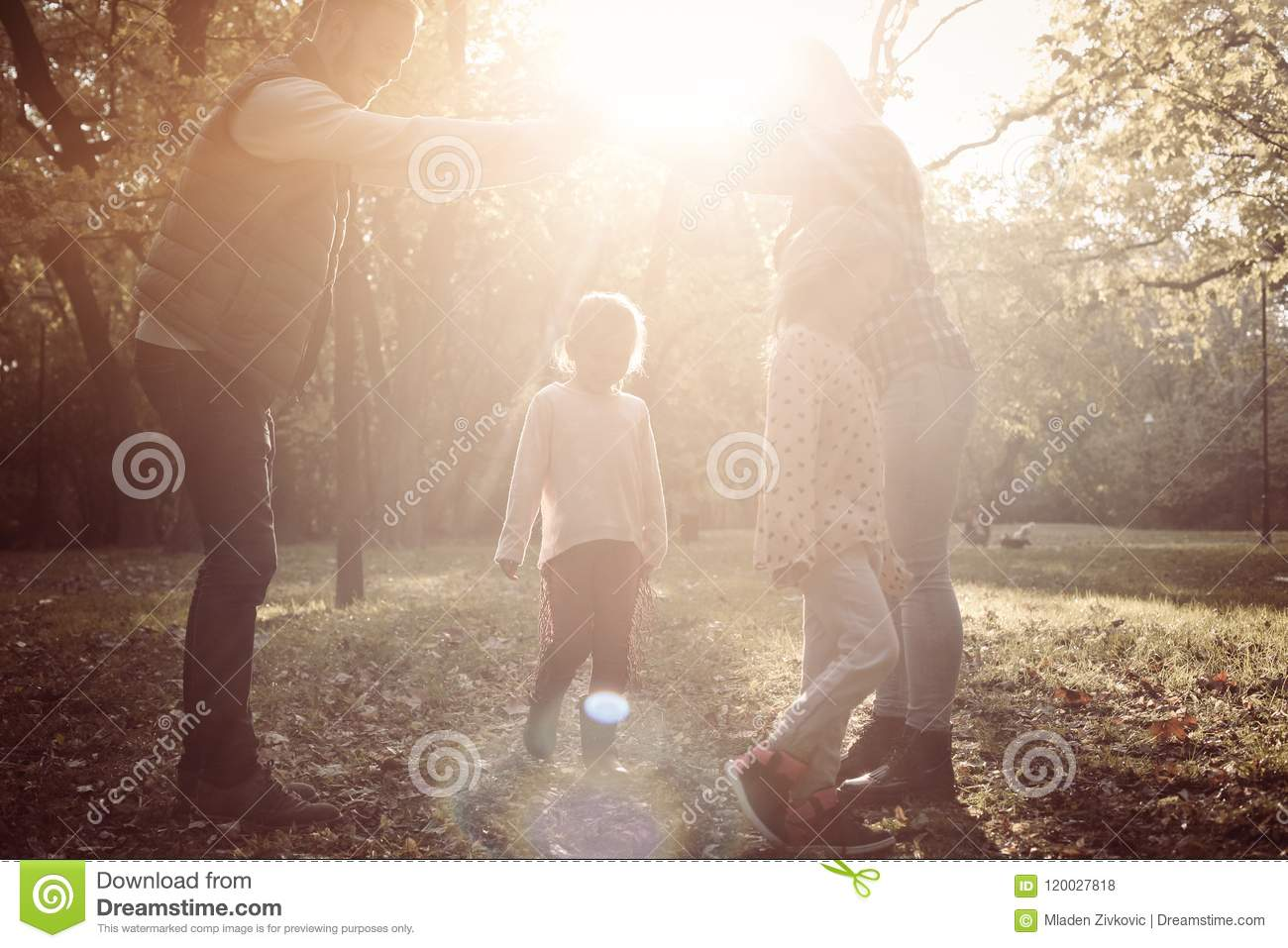 Happy parents with two child playing together in nature.