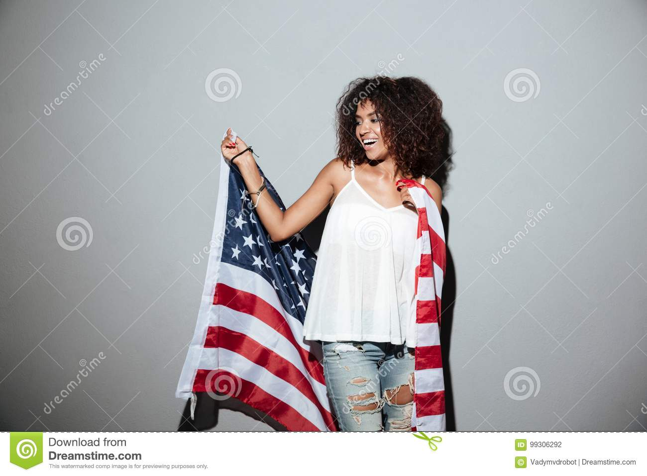 Happy patriotic african woman holding US flag