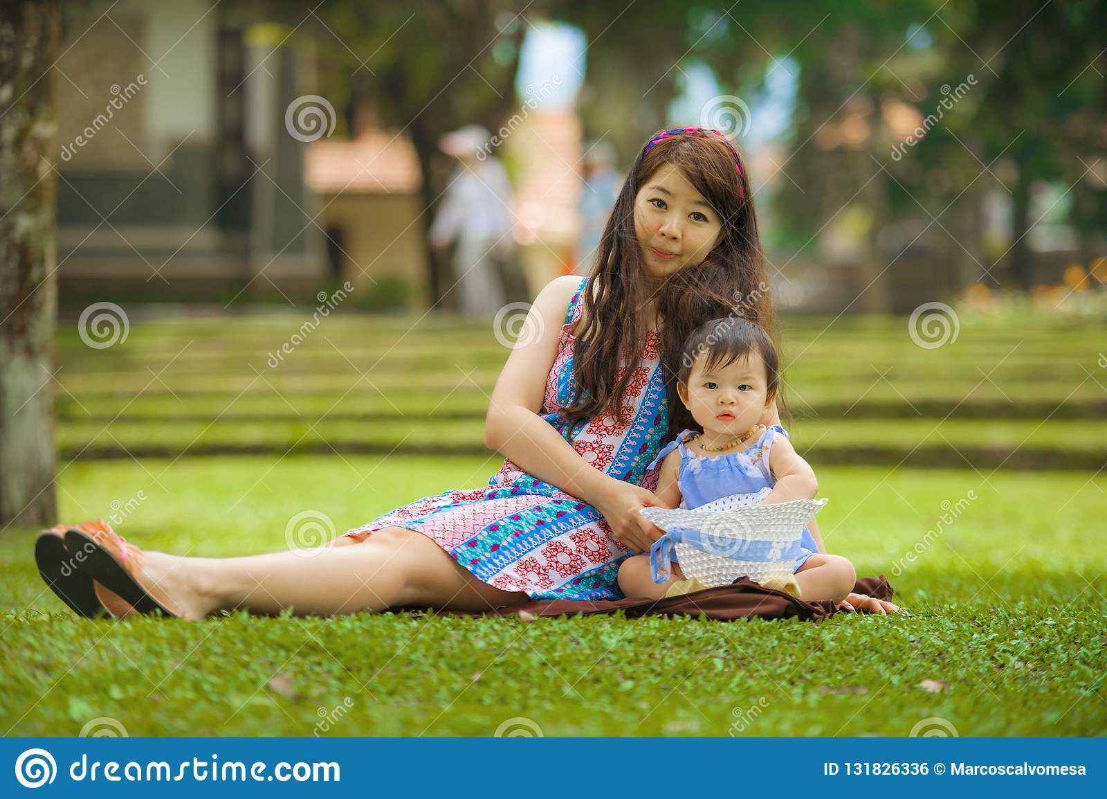 Happy and playful Asian Chinese woman as loving mother enjoying with sweet and beautiful daughter baby girl sitting together