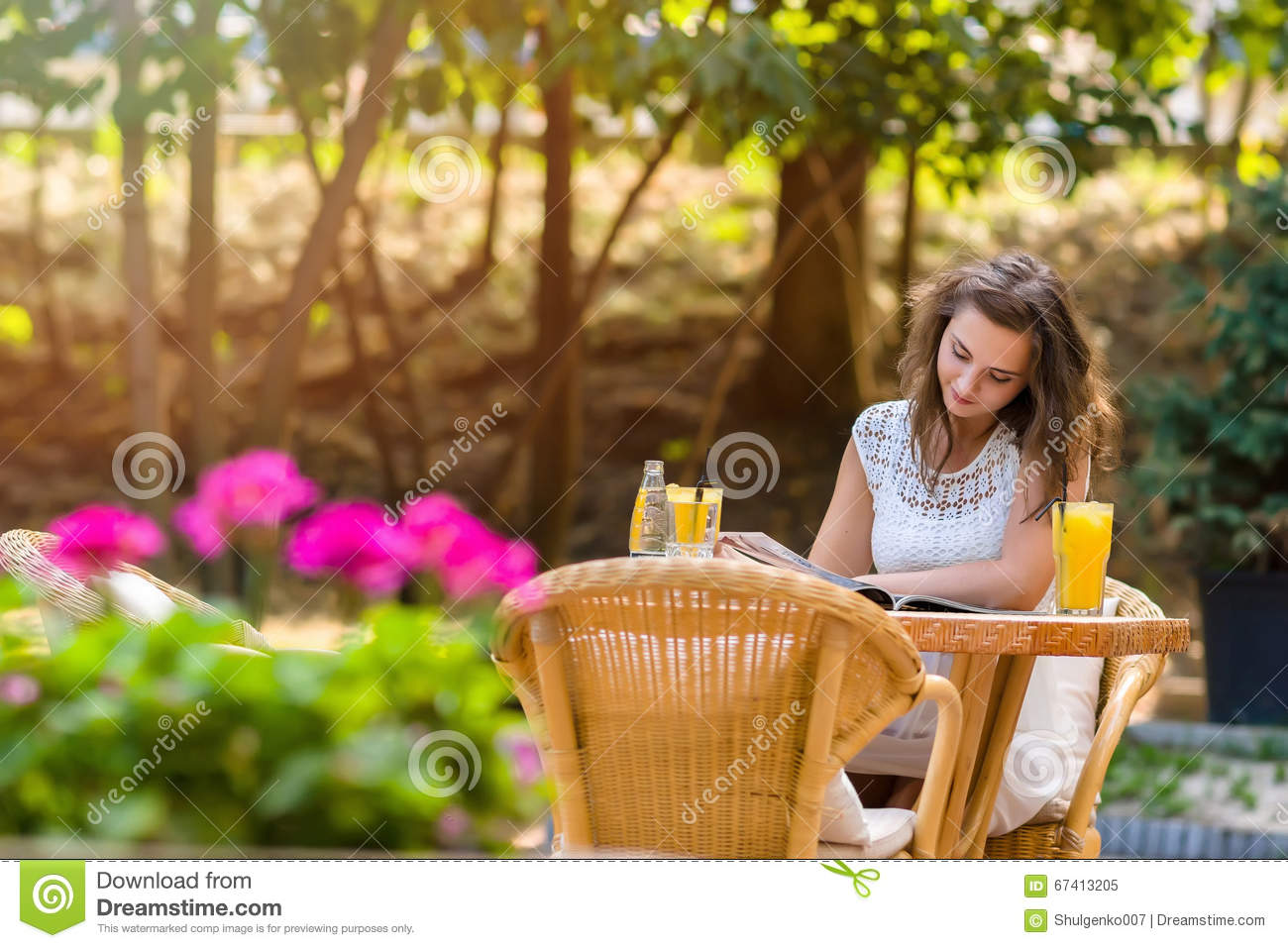 Happy, positive, beautiful, elegance girl sitting at cafe table outdoors.