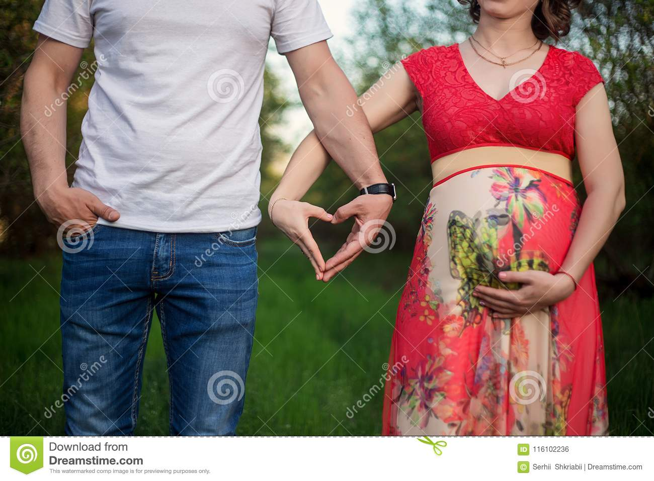 A happy pregnant couple made from hands made of a heart