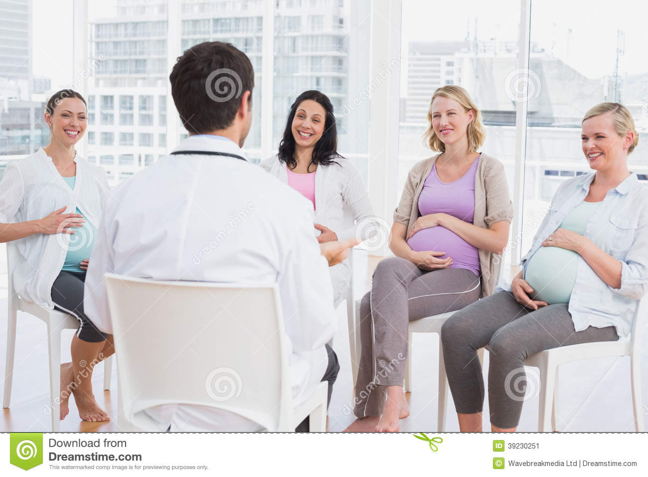 Happy pregnant women listening to doctor at antenatal class