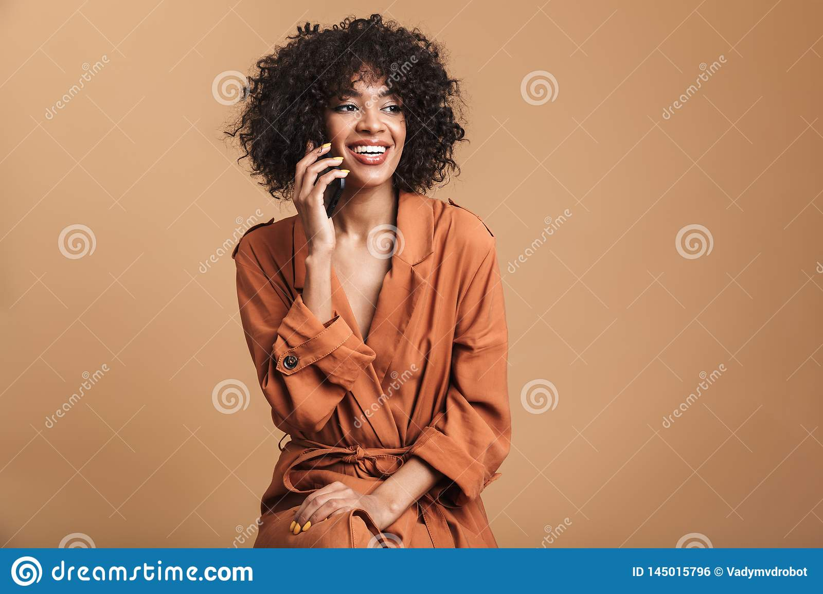 Happy pretty african woman talking by smartphone and looking away