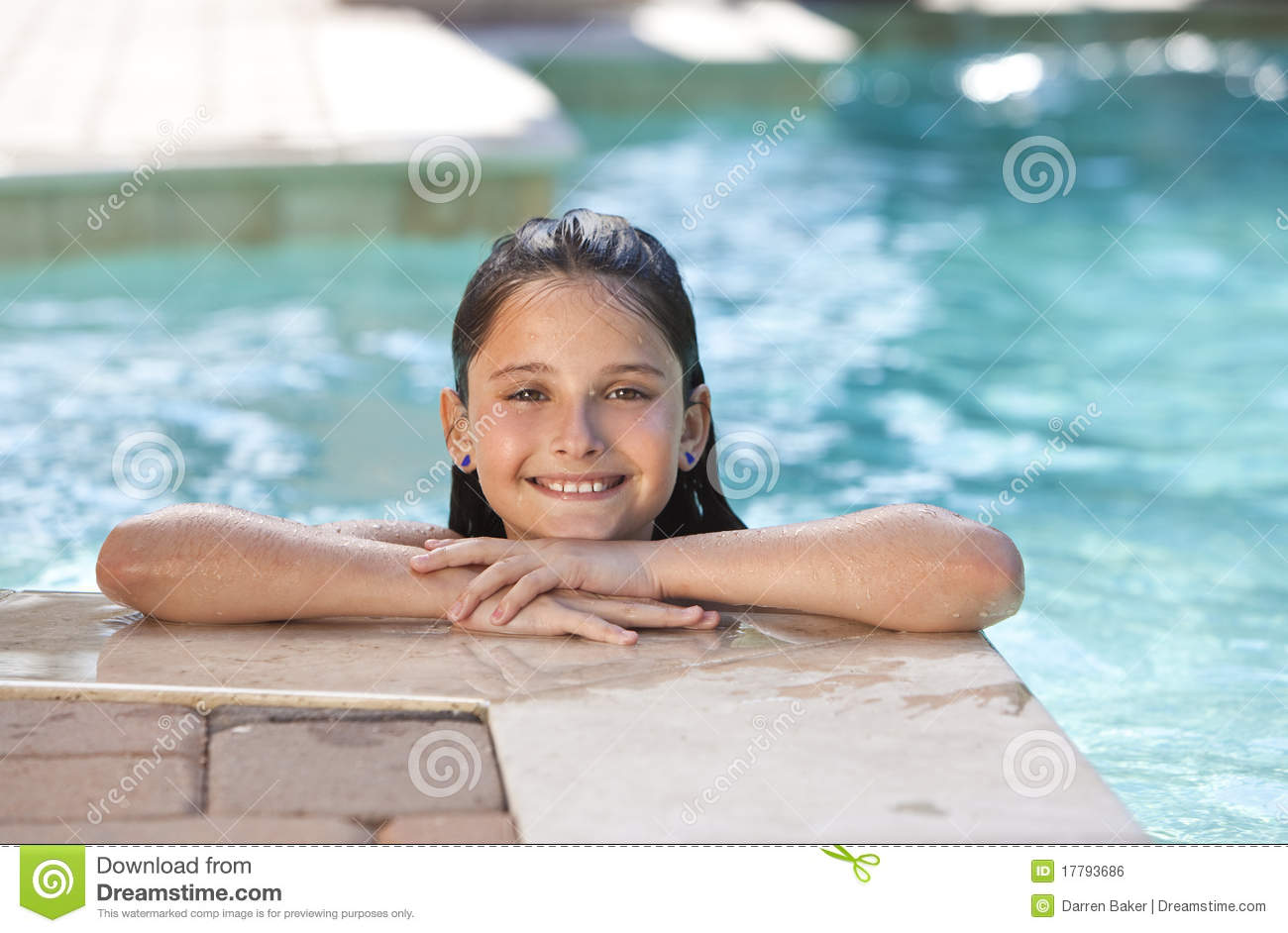 young girl child relaxing and smiling on the side of a swimming pool ...