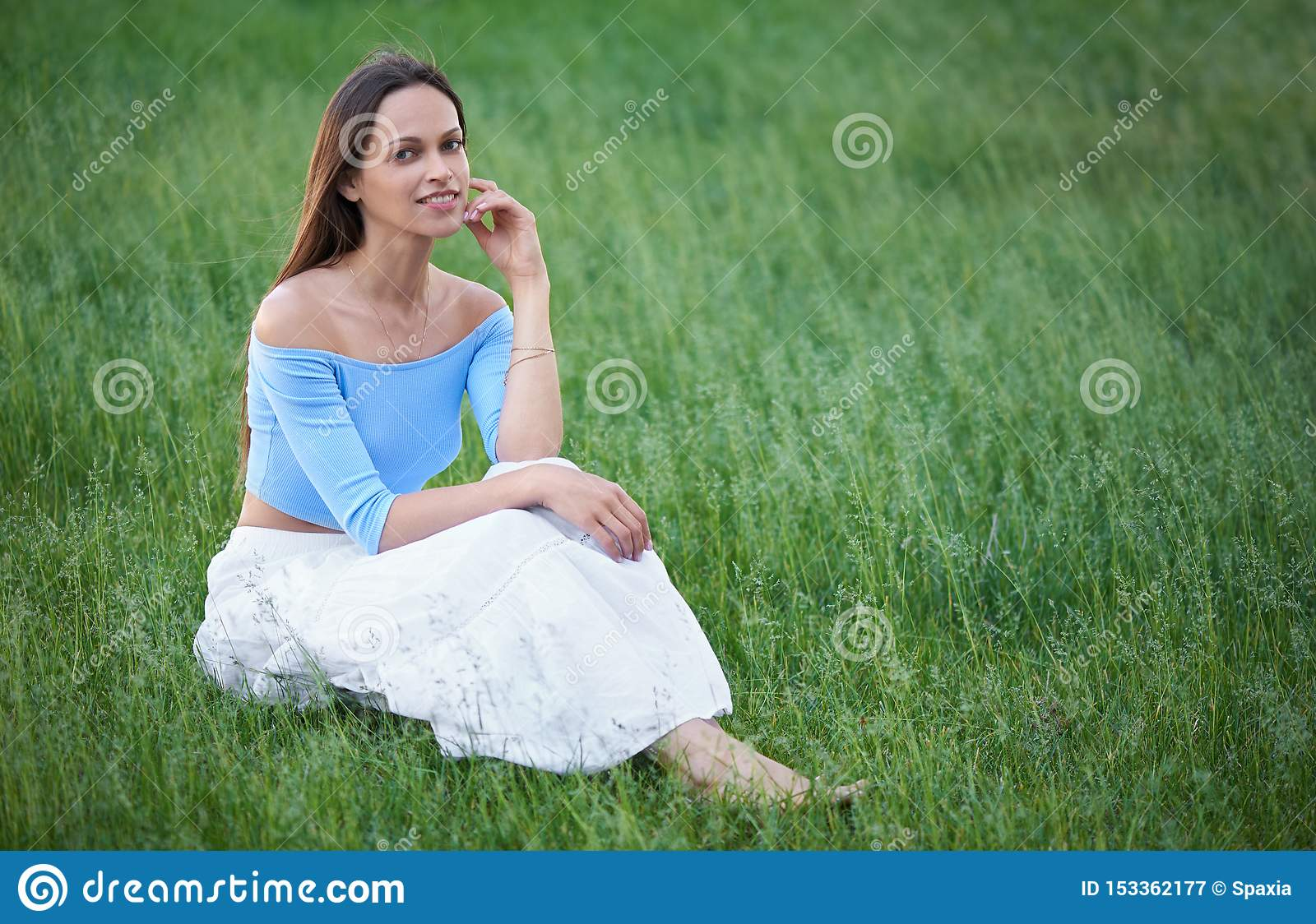 Happy pretty woman is sitting on a grass