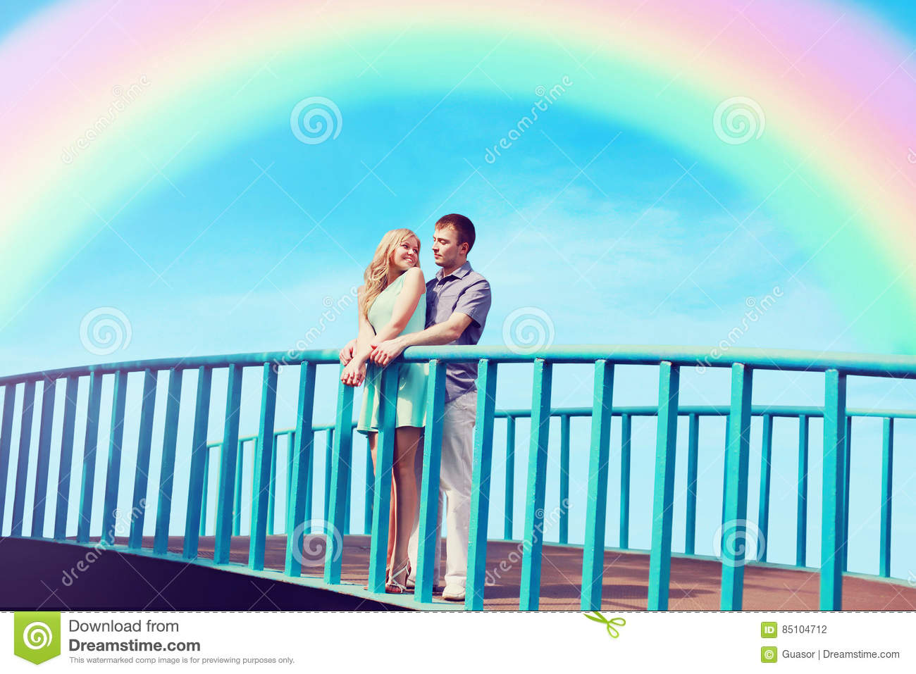 Happy pretty young couple in love on the bridge over blue sky and colorful rainbow. Valentine`s day and relationships