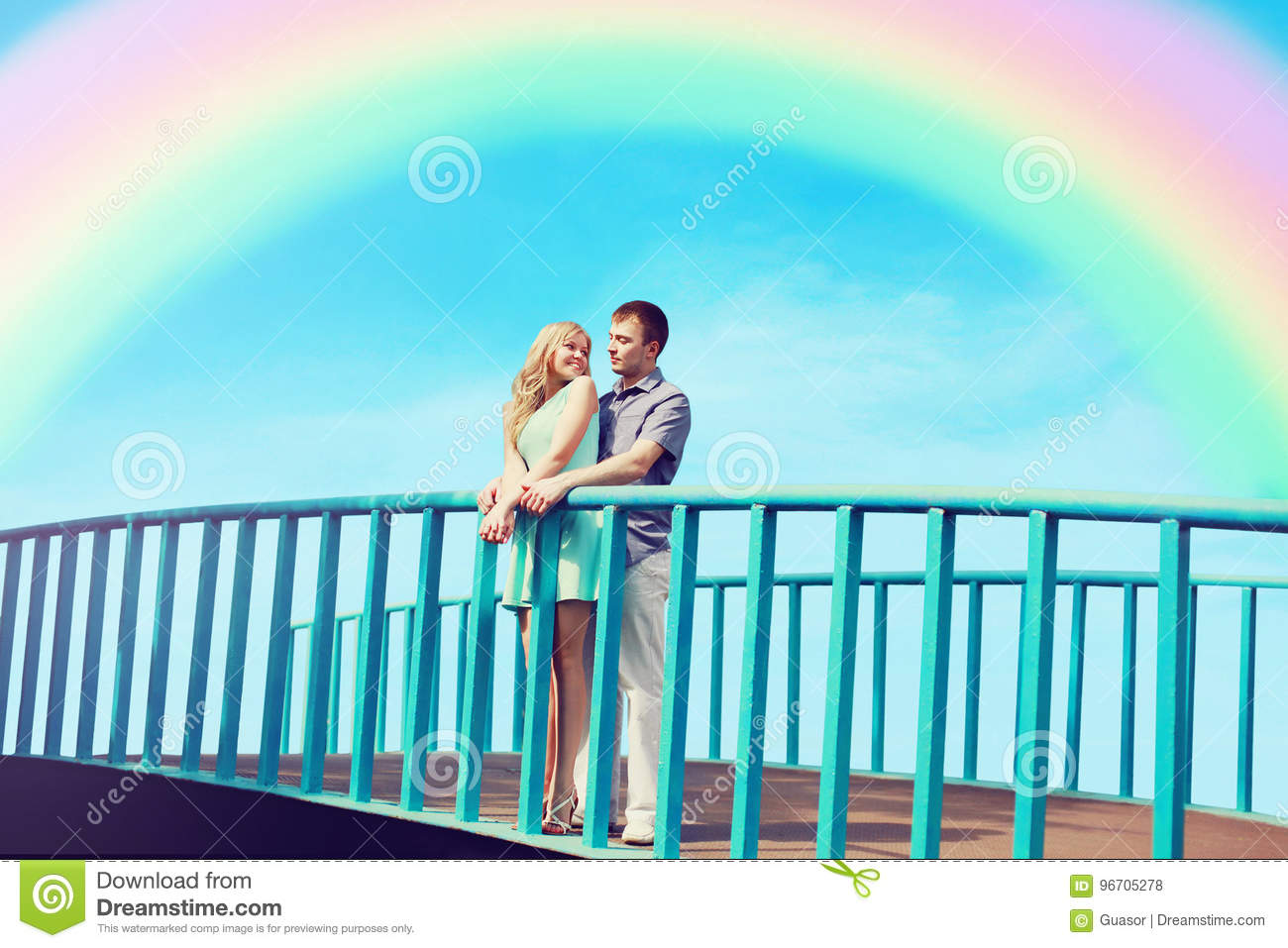 Happy pretty young loving couple stands on the bridge