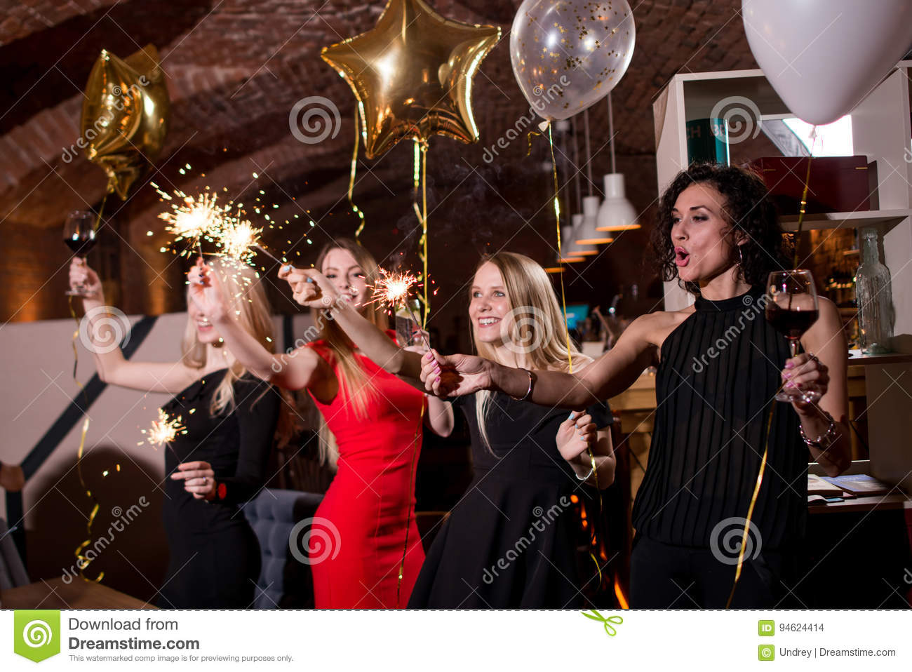 Happy pretty young women holding firework sparklers, balloons, glasses of wine celebrating a holiday in restaurant with