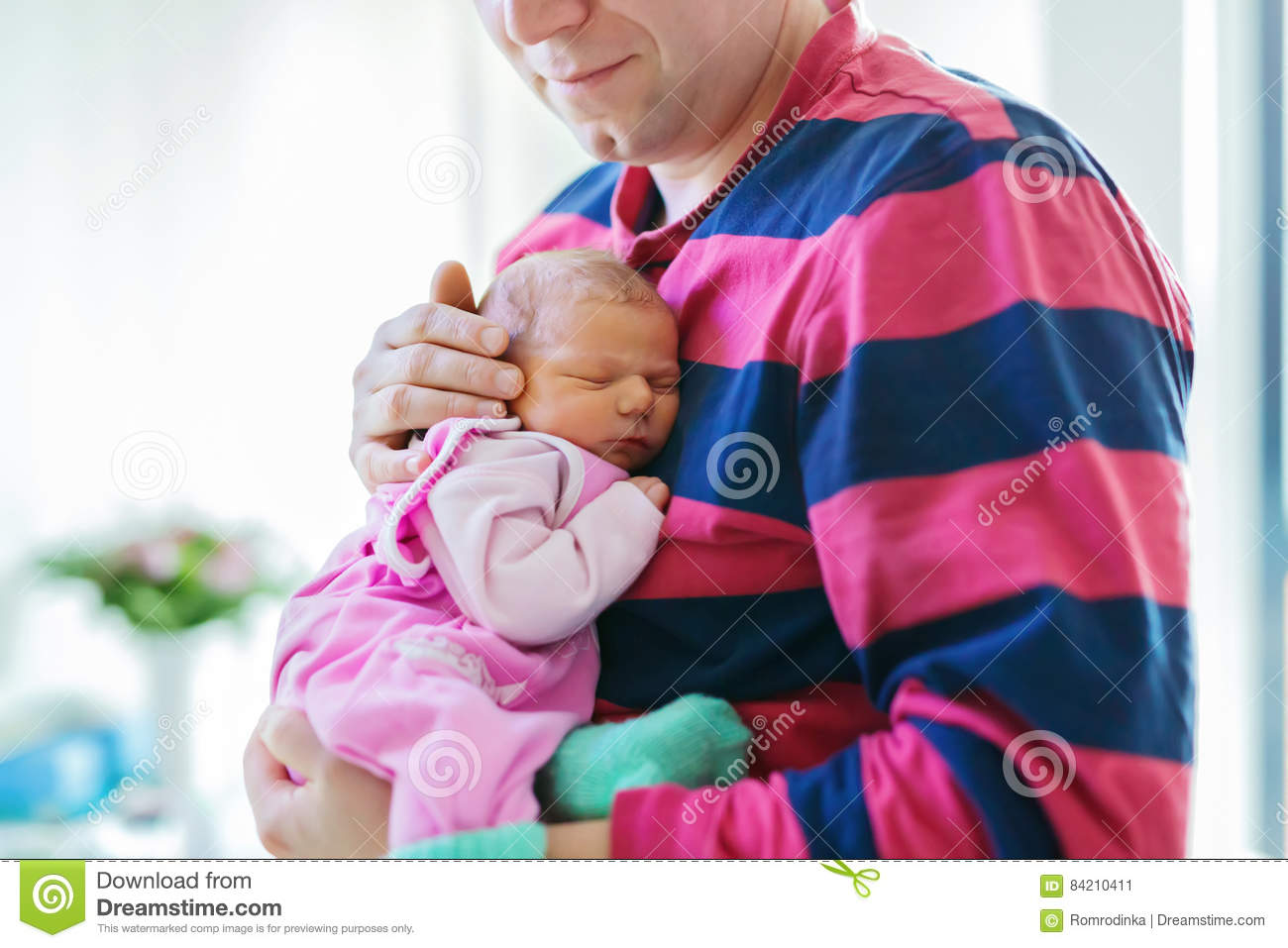 Happy proud young father holding his sleeping newborn baby daughter