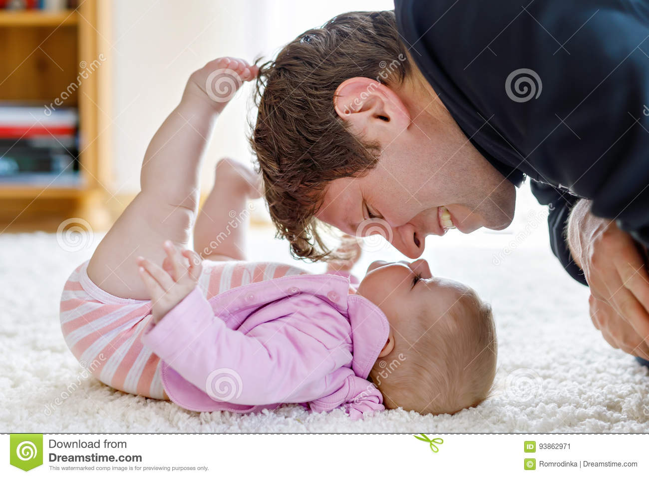 Happy proud young father with newborn baby daughter, family portrait together