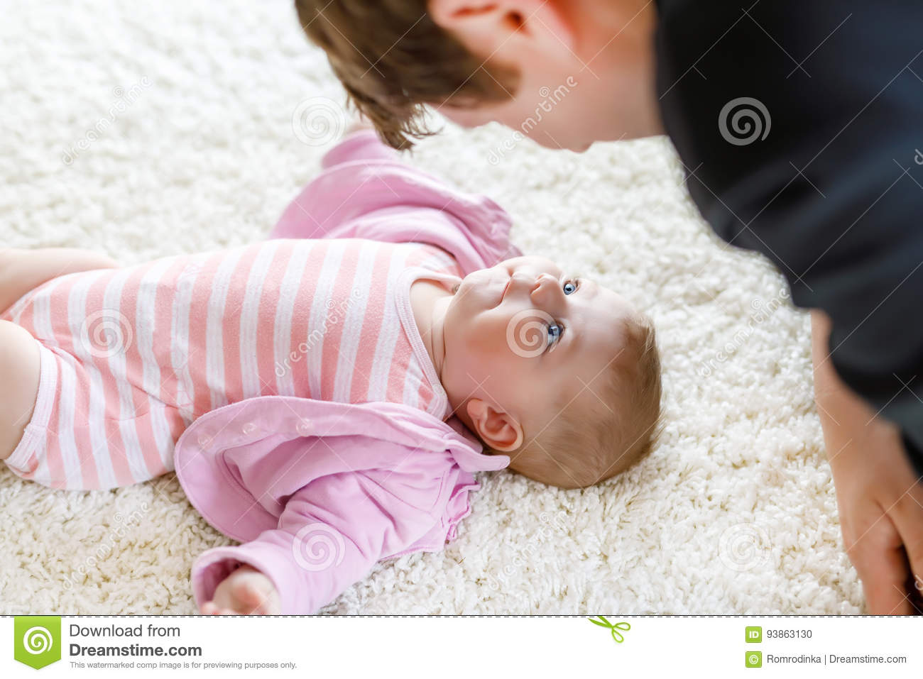 Happy proud young father having fun with newborn baby daughter family portrait together dad with baby girl love new born child looking on dad