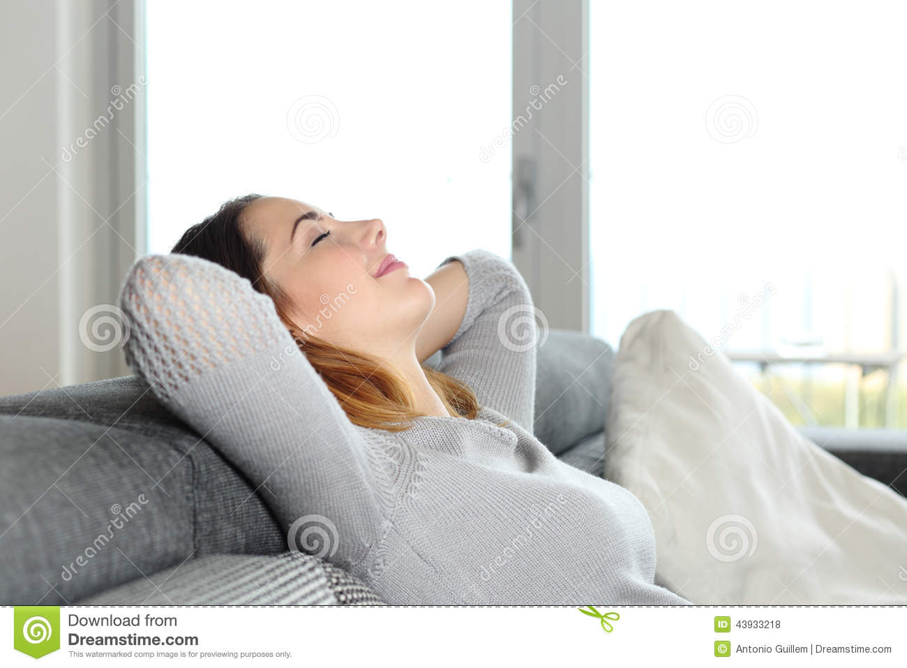 happy relaxed woman resting couch home arms head 43933218