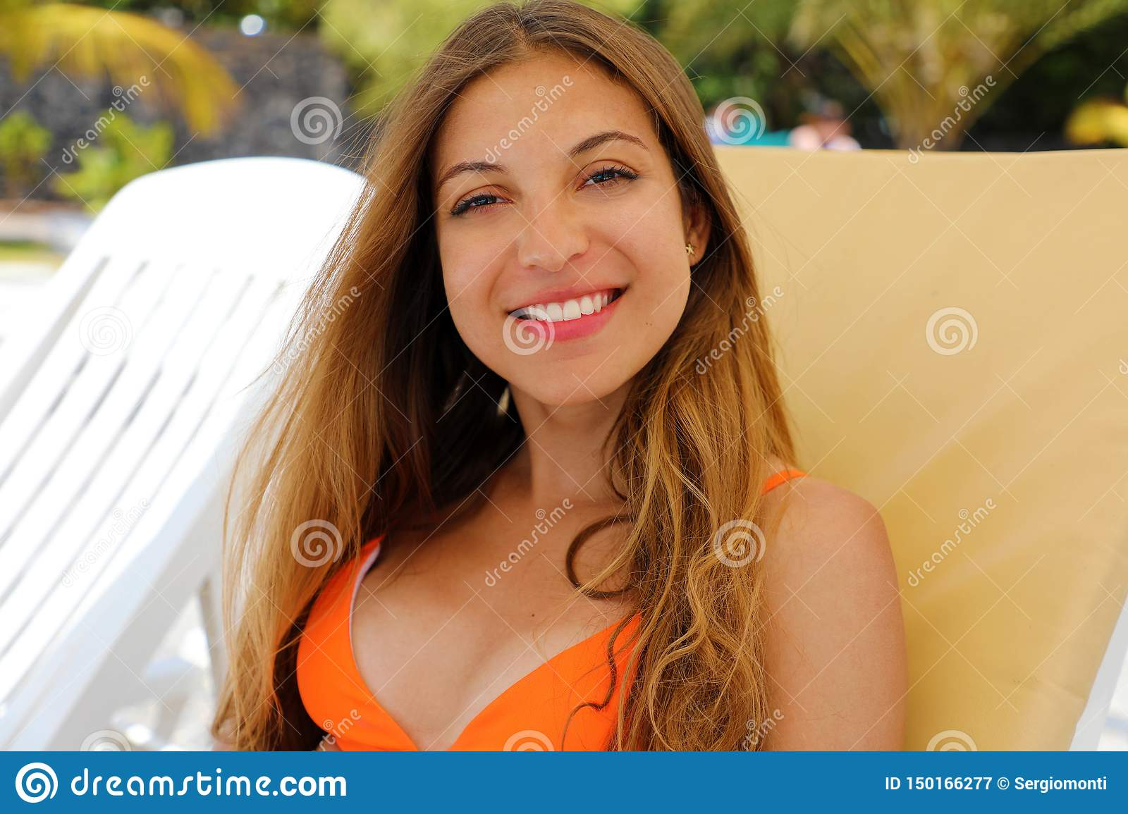 Happy relaxing woman sitting comfortable and looking at camera. Resting beautiful smiling girl enjoying her holidays in Tenerife
