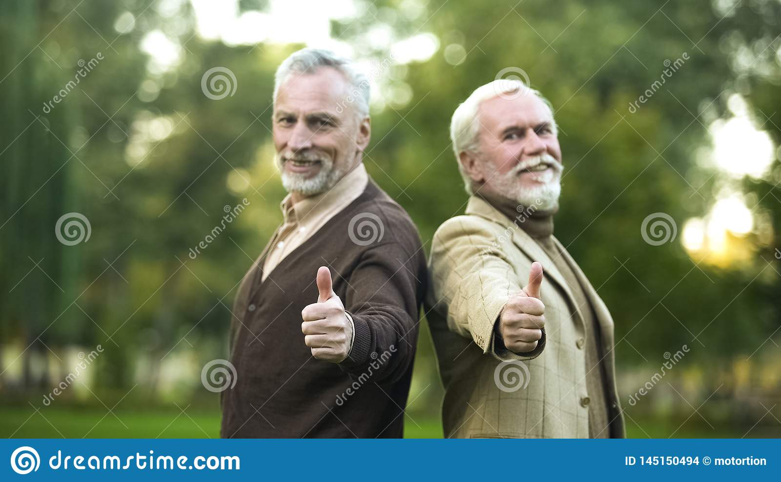 Happy retired gentlemen showing thumbs up and looking in camera, companions