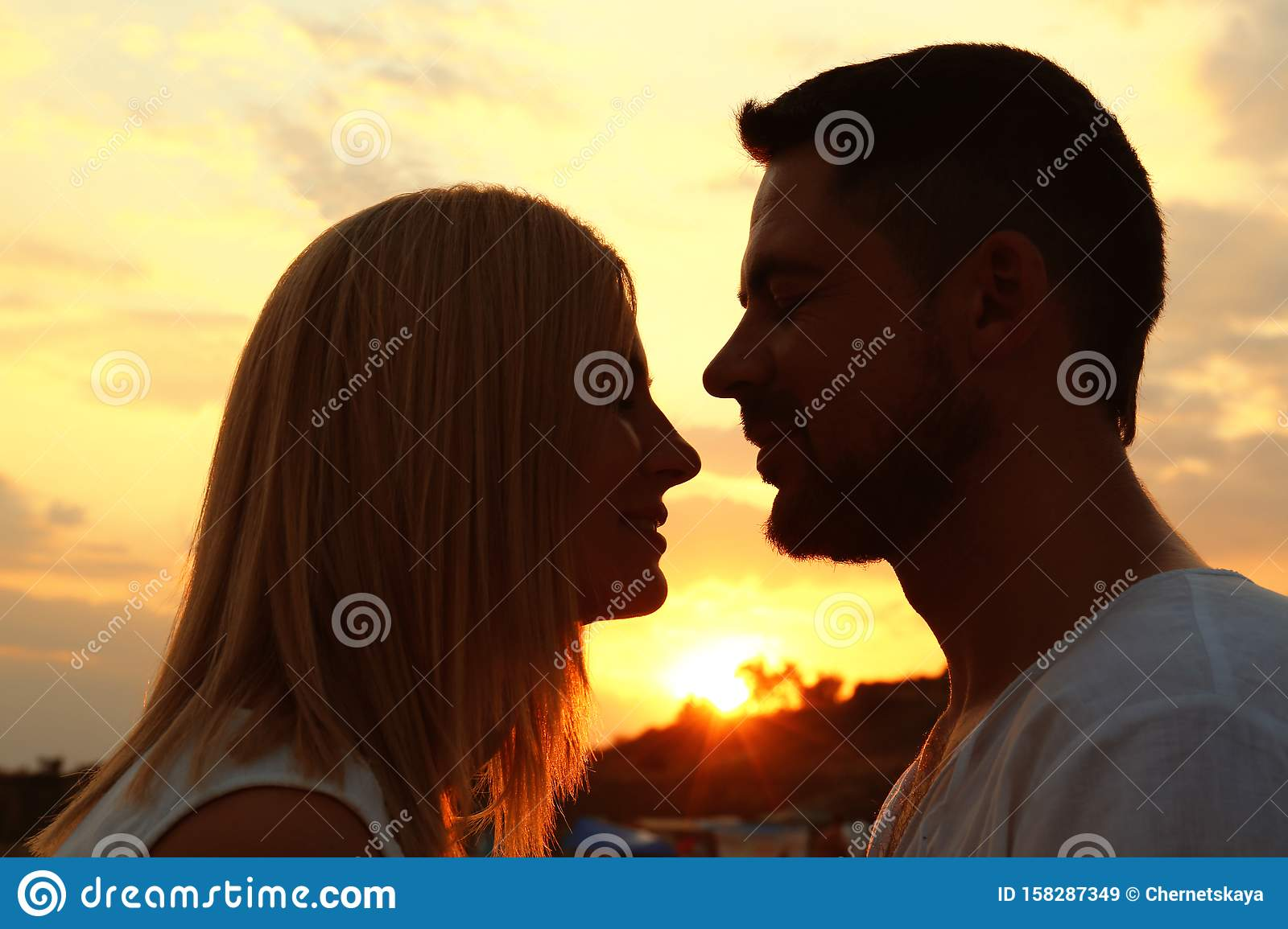 Happy romantic couple spending time together at sunset
