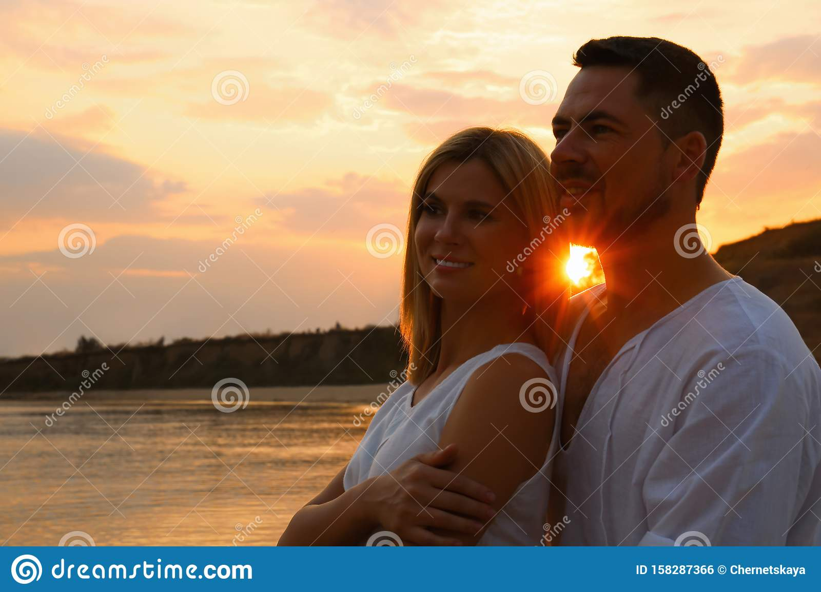 Happy romantic couple spending time together on beach at sunset