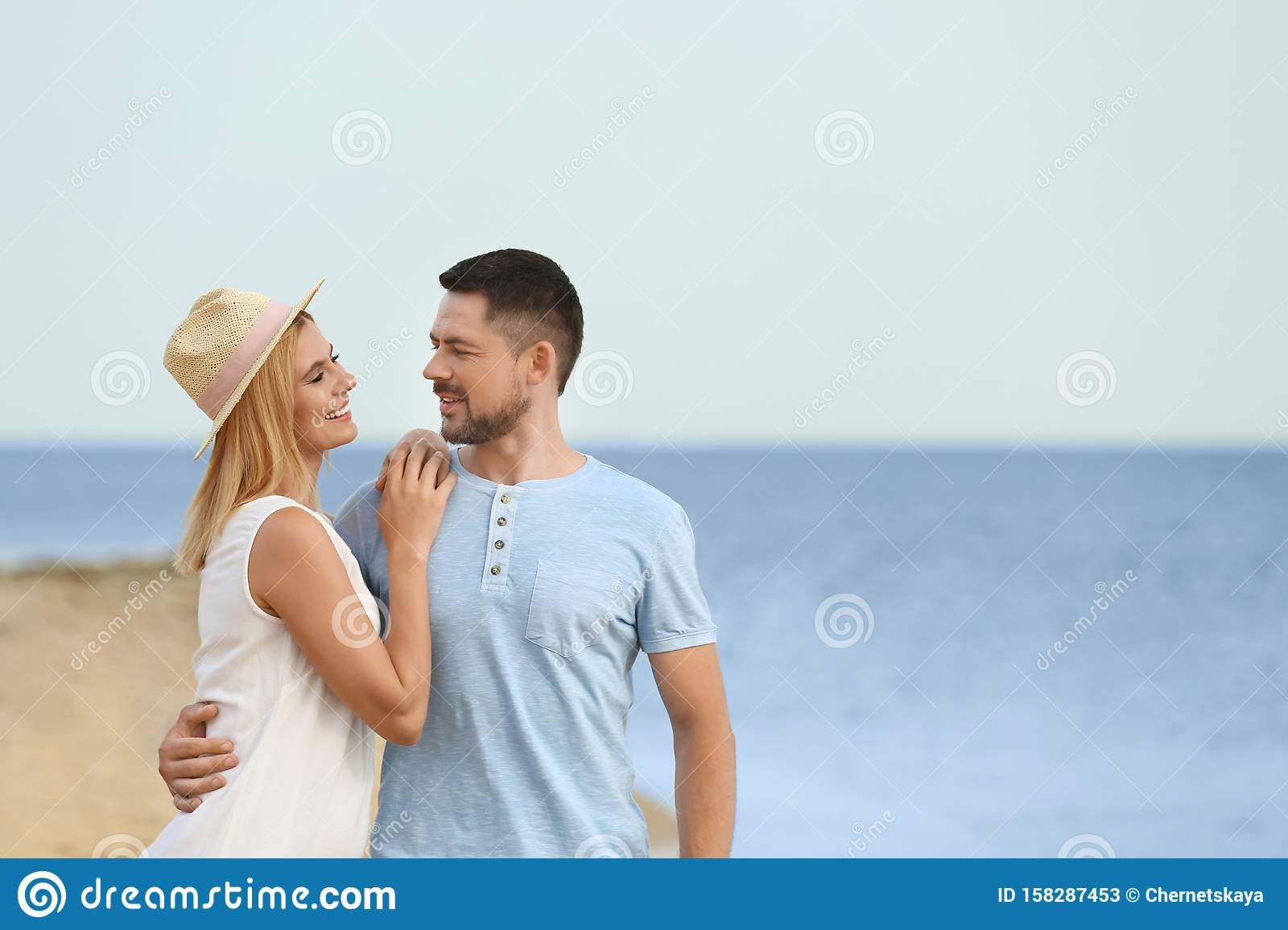 Happy romantic couple time together on beach, space for text