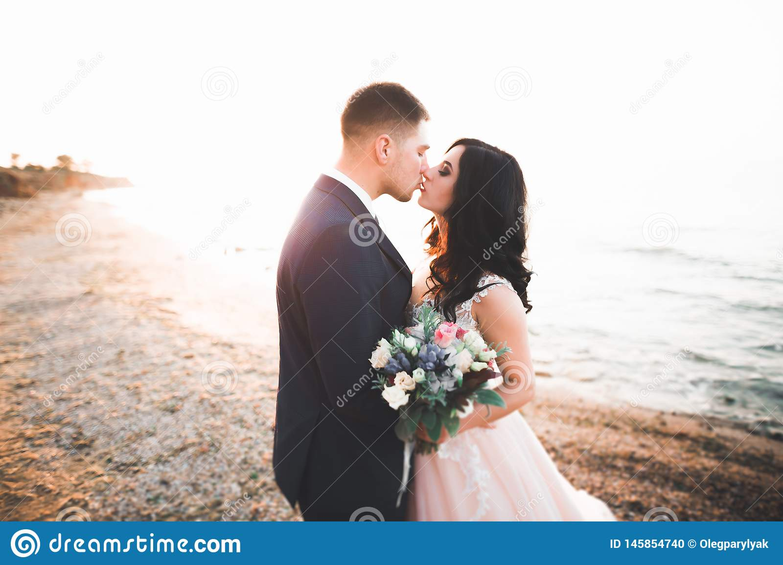 Happy And Romantic Scene Of Just Married Young Wedding Couple Posing On Beautiful Beach Stock Photo Image Of Bride Flowers 145854740