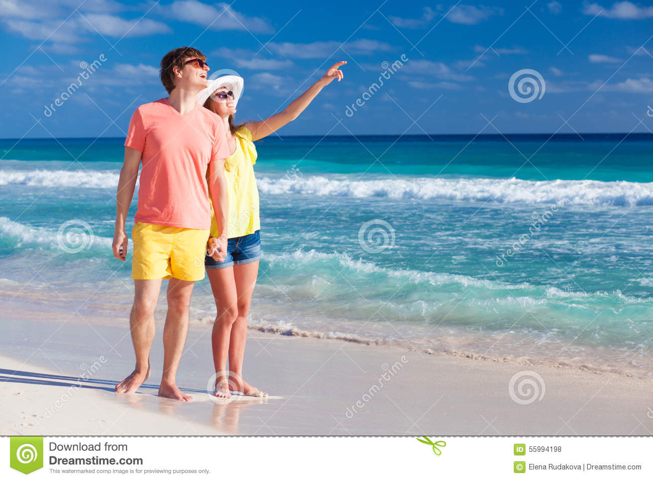 Happy romantic young couple pointing at the sky