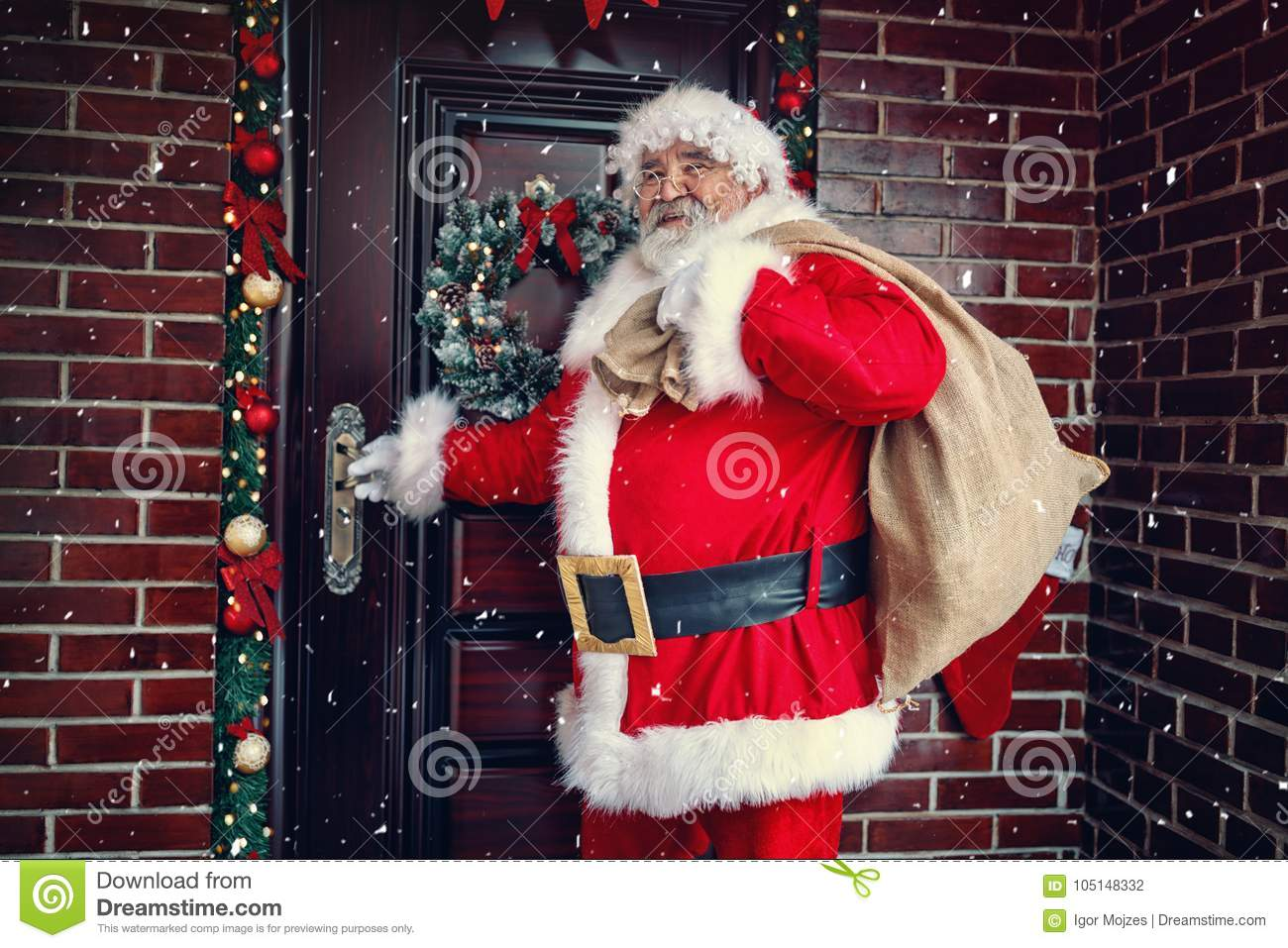 Happy Santa Claus arrives with present on large bag at in night