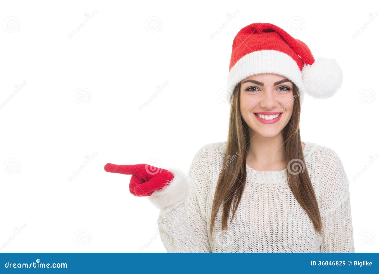 Happy cute Caucasian teenage girl with Santa hat pointing sideways ...