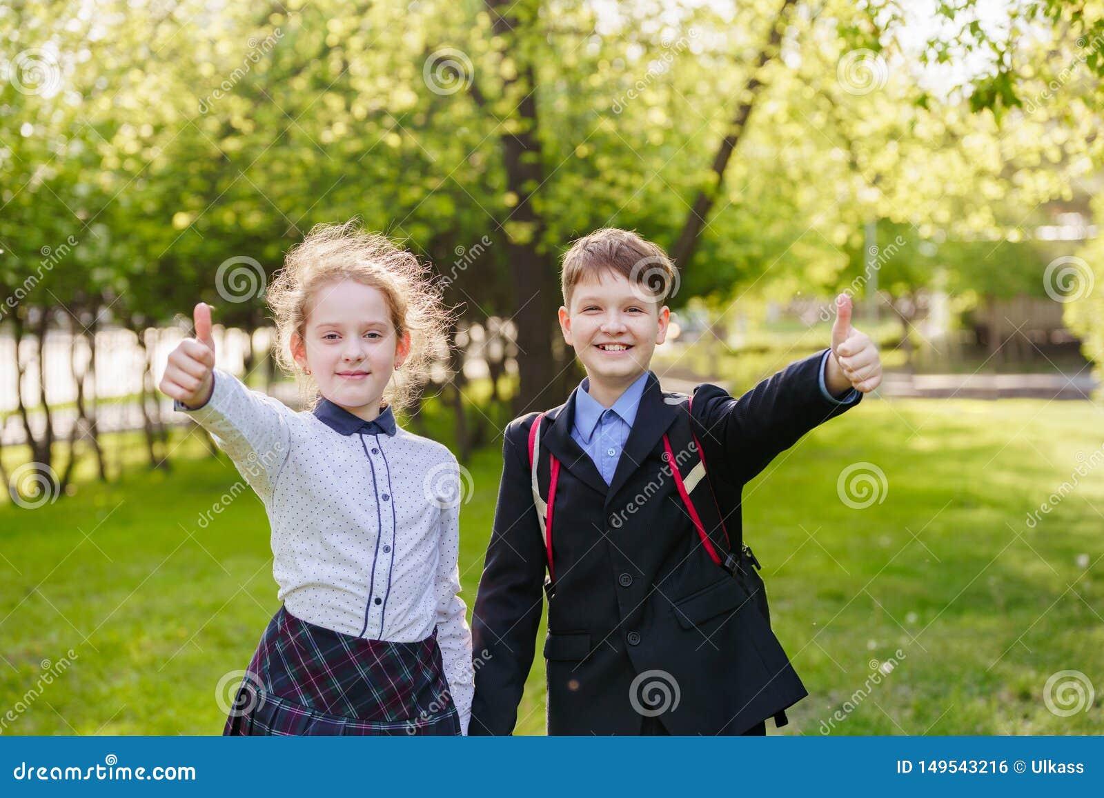 Happy school children giving a thumbs up