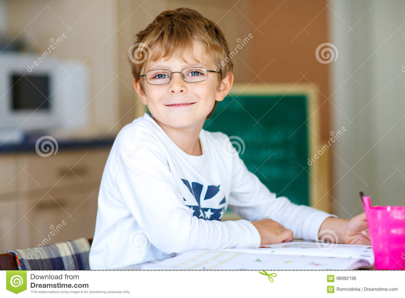 91c72ce5784 Portrait of cute happy school kid boy with glasses at home making homework. Little  child writing with colorful pencils