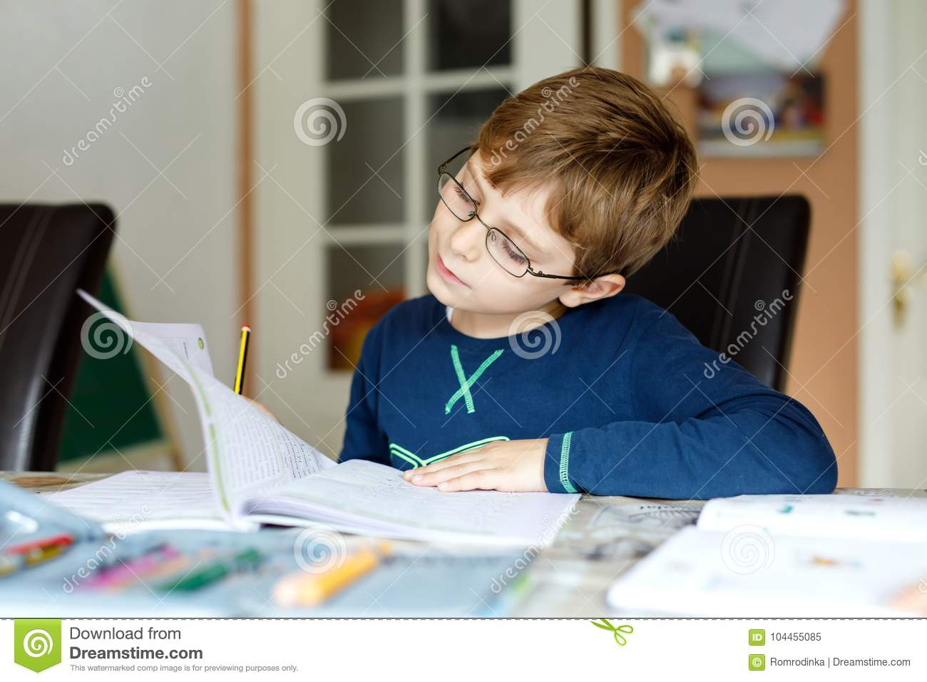 fc95540eac9 Portrait of cute school kid boy wearing glasses at home making homework.  Little concentrated child writing with colorful pencils